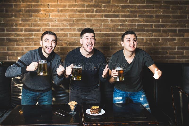 Τρία άτομα με την μπύρα χαίρονται τη νίκη της αγαπημένης ομάδας τους πριν από το στόχο για το μπαρ Το μπαρ πίνει την μπύρα στοκ φωτογραφία με δικαίωμα ελεύθερης χρήσης