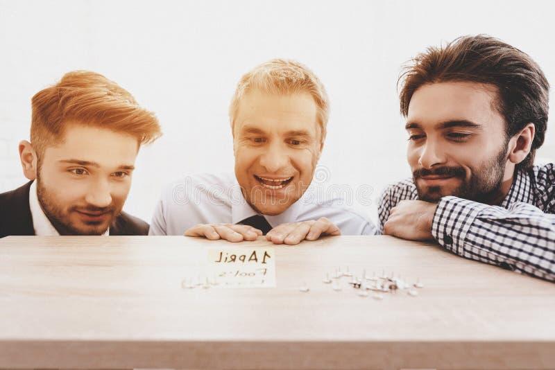 Τρία άτομα που εξετάζουν τα γραφείου κουμπιά στον πίνακα στοκ εικόνες με δικαίωμα ελεύθερης χρήσης