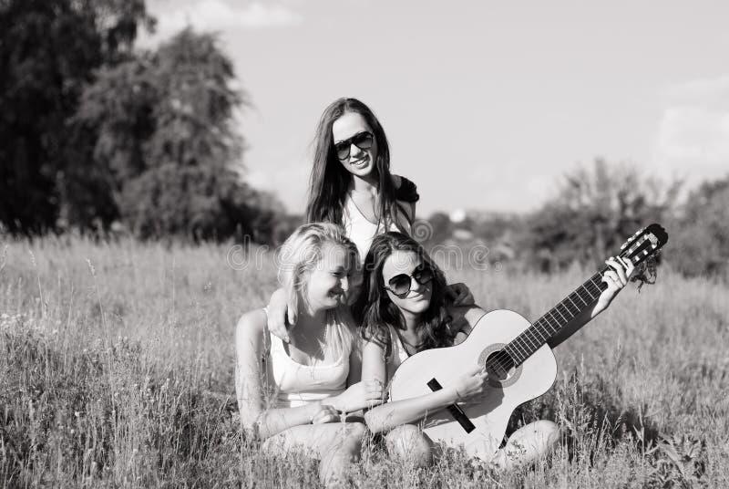 Τρία έφηβη νέων που παίζουν την κιθάρα στοκ φωτογραφία