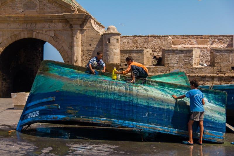 Τρία αγόρια πλένουν το μπλε αλιευτικό σκάφος κοντά στο medina στοκ φωτογραφία