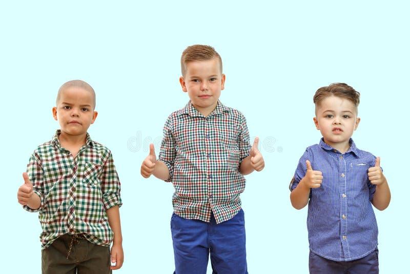 Τρία αγόρια στέκονται μαζί στο άσπρο υπόβαθρο και κρατούν τους αντίχειρές τους επάνω στοκ εικόνες