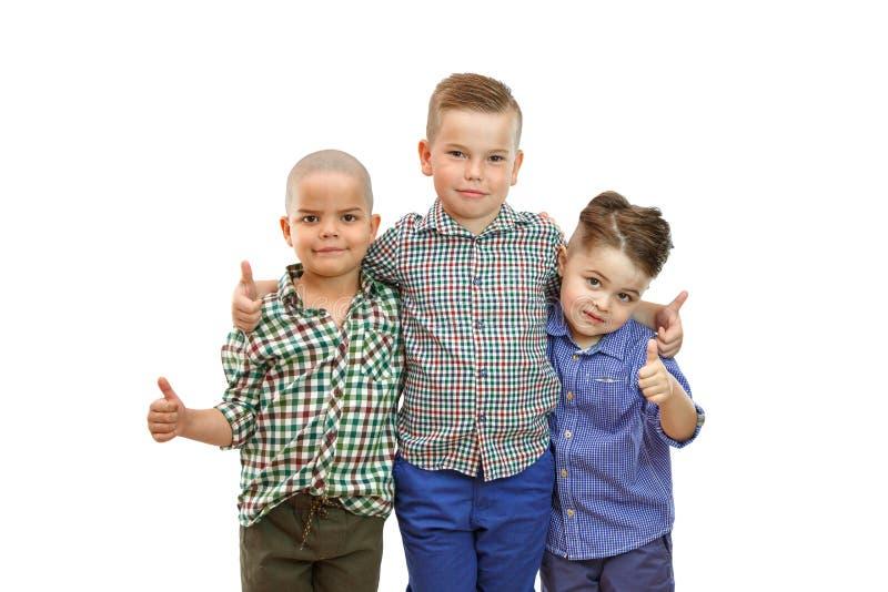 Τρία αγόρια στέκονται μαζί στο άσπρο υπόβαθρο και κρατούν τους αντίχειρές τους επάνω στοκ φωτογραφίες