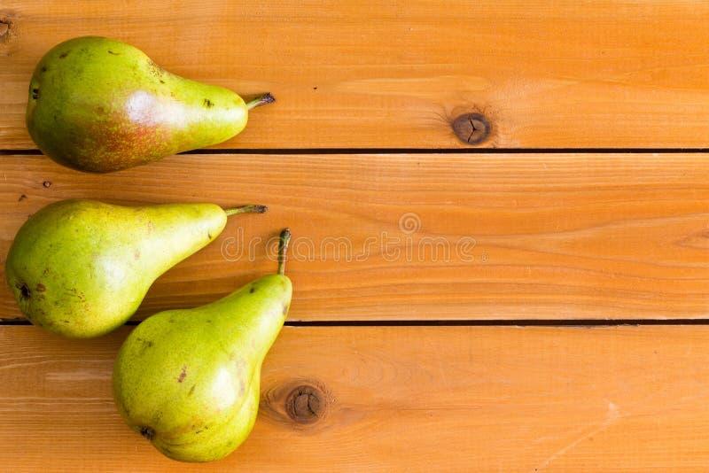 Τρία ακατέργαστα πράσινα αχλάδια στον επιτραπέζιο ξύλινο πίνακα στοκ φωτογραφία με δικαίωμα ελεύθερης χρήσης