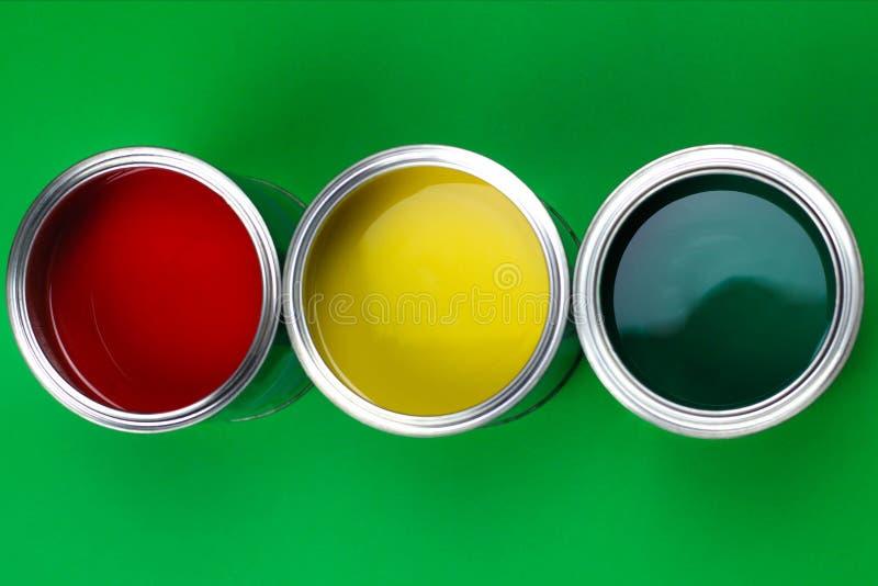 Τρία ανοικτά δοχεία του χρώματος σε ένα πράσινο υπόβαθρο στοκ φωτογραφίες με δικαίωμα ελεύθερης χρήσης