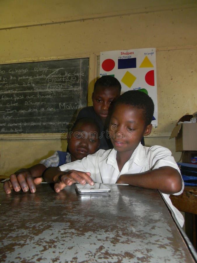 Τρία αρχικά schoolkids που χρησιμοποιούν την ταμπλέτα στην τάξη στοκ εικόνες