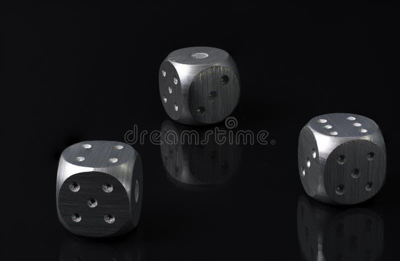 Τρία ασημένιο παιχνίδι Dics που βάζει στο μαύρο γυαλί με το μαύρο υπόβαθρο στοκ εικόνα