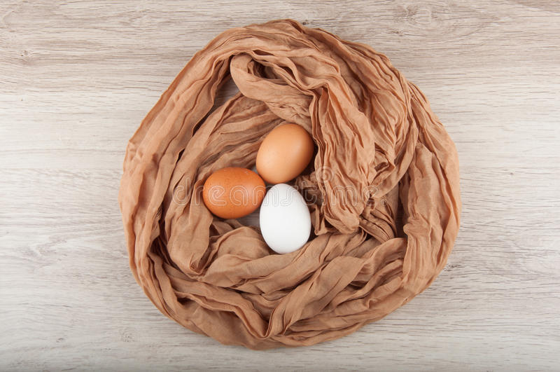 Τρία αυγά κοτόπουλου στη φωλιά φιαγμένη από καφετή σάκο υφασμάτων στοκ εικόνες με δικαίωμα ελεύθερης χρήσης