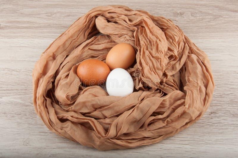 Τρία αυγά κοτόπουλου στη φωλιά φιαγμένη από σάκο υφασμάτων στοκ φωτογραφίες