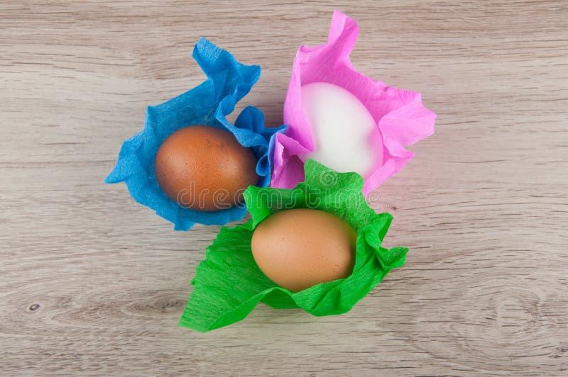 Τρία αυγά κοτόπουλου στο χρωματισμένο περιτύλιγμα εγγράφου που βάζει στον ξύλινο πίνακα Τοπ όψη στοκ φωτογραφία με δικαίωμα ελεύθερης χρήσης