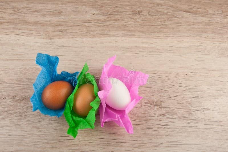 Τρία αυγά κοτόπουλου στο χρωματισμένο περιτύλιγμα εγγράφου που βάζει στον ξύλινο πίνακα Διάστημα για το κείμενο στοκ εικόνα με δικαίωμα ελεύθερης χρήσης