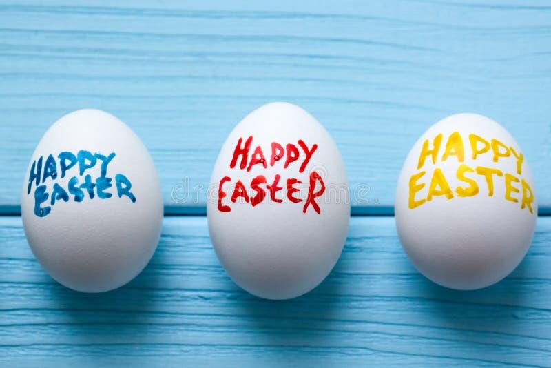 Τρία αυγά Πάσχας με τους τίτλους ` ευτυχές Πάσχα ` χρώματος που γράφεται από τη βούρτσα χρωμάτων είναι στο μπλε χρωματισμένο ξύλι στοκ εικόνες