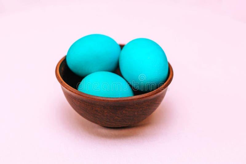 Τρία αυγά Πάσχας του τυρκουάζ χρώματος σε ένα ξύλινο πιάτο σε ένα μαλακό ρόδινο υπόβαθρο στοκ φωτογραφία με δικαίωμα ελεύθερης χρήσης