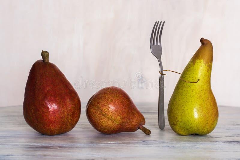 Τρία αχλάδια σε έναν ξύλινο πίνακα Εννοιολογικές φωτογραφίες Ένα αχλάδι με ένα δίκρανο Σύνθεση με τα αχλάδια αχλάδια τρία στοκ εικόνα