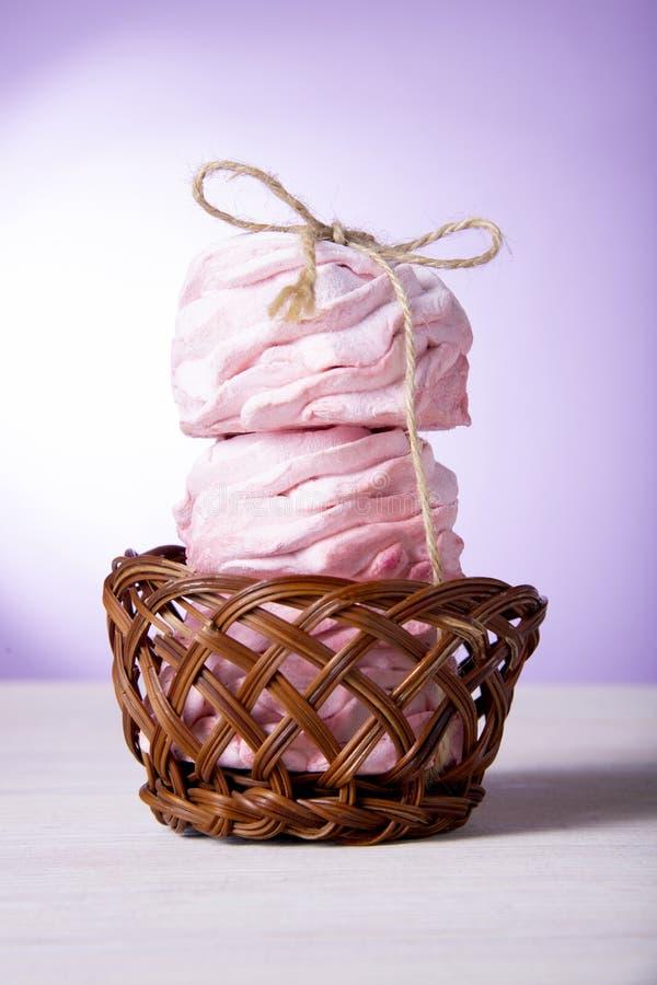 Τρία γλυκά ρόδινα κέικ σε ένα ξύλινο καλάθι Ρόδινα marshmallows κερασιών στοκ φωτογραφία