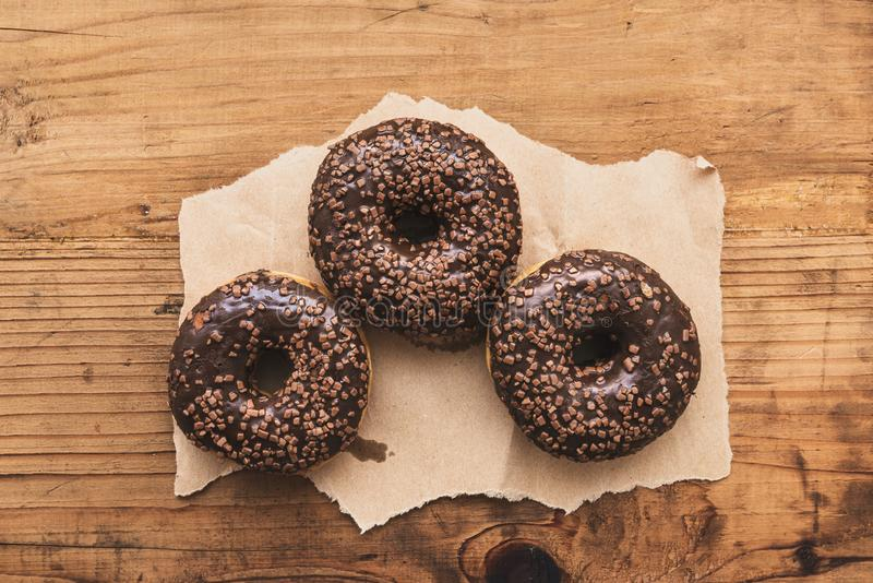 Τρία γλυκά doughnuts με την κρέμα και crumbs σοκολάτας στοκ φωτογραφία