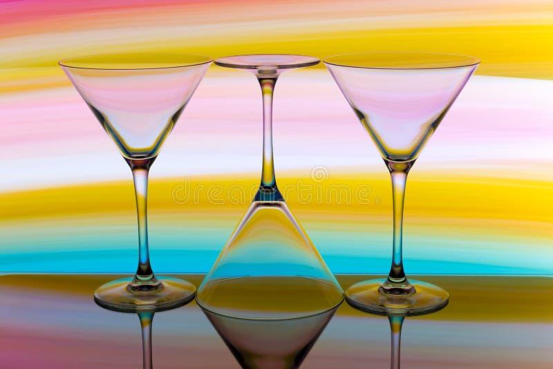 Τρία γυαλιά κοκτέιλ/martini σε μια σειρά με ένα ουράνιο τόξο του χρώματος πίσω από τους στοκ εικόνα
