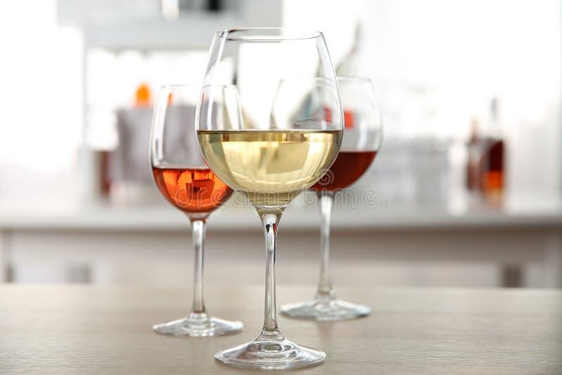 Τρία γυαλιά με το κρασί στον πίνακα κουζινών στοκ εικόνες