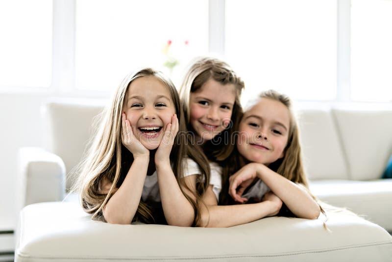 Τρία ελκυστικά έφηβη στα περιστασιακά ενδύματα που προσέχουν τη TV στο σπίτι στοκ εικόνες με δικαίωμα ελεύθερης χρήσης
