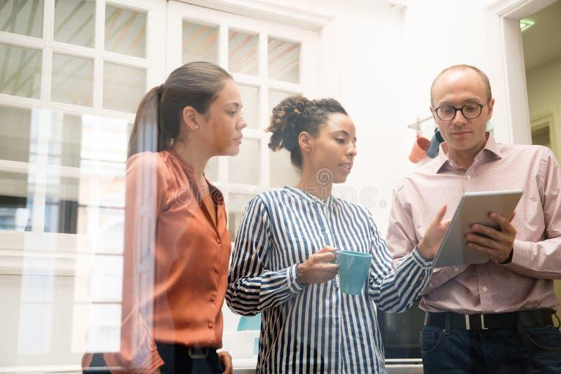 Τρία επιχειρησιακά μέλη ομάδας που κρατούν μια ταμπλέτα PC στοκ εικόνα με δικαίωμα ελεύθερης χρήσης