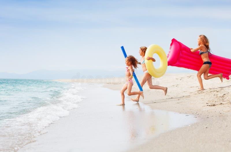 Τρία ευτυχή κορίτσια που τρέχουν μαζί στην τροπική θάλασσα στοκ φωτογραφίες