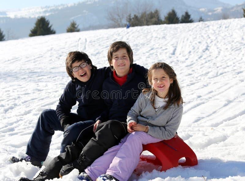 Τρία ευτυχή παιδιά στο χιόνι κατά τη διάρκεια των καλοκαιρινών διακοπών στοκ εικόνες