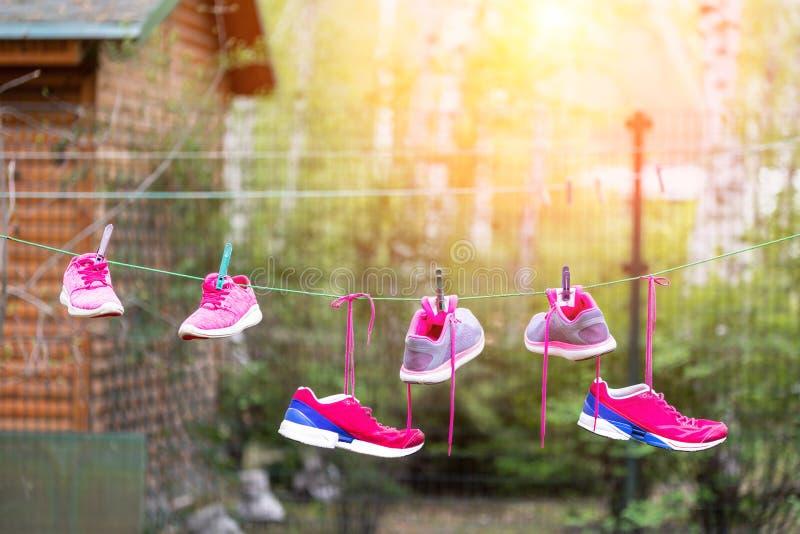 Τρία ζευγάρια των φωτεινών πάνινων παπουτσιών αθλητικής ικανότητας κρέμασαν στο clothespin στο κατώφλι μετά από το πλυντήριο υπαί στοκ φωτογραφία με δικαίωμα ελεύθερης χρήσης