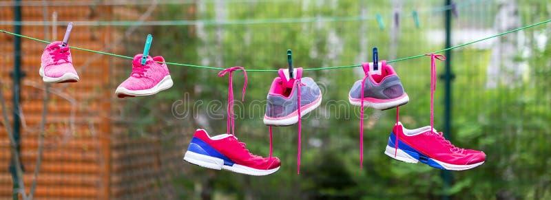 Τρία ζευγάρια των φωτεινών πάνινων παπουτσιών αθλητικής ικανότητας κρέμασαν στο clothespin στο κατώφλι μετά από το πλυντήριο υπαί στοκ εικόνα με δικαίωμα ελεύθερης χρήσης