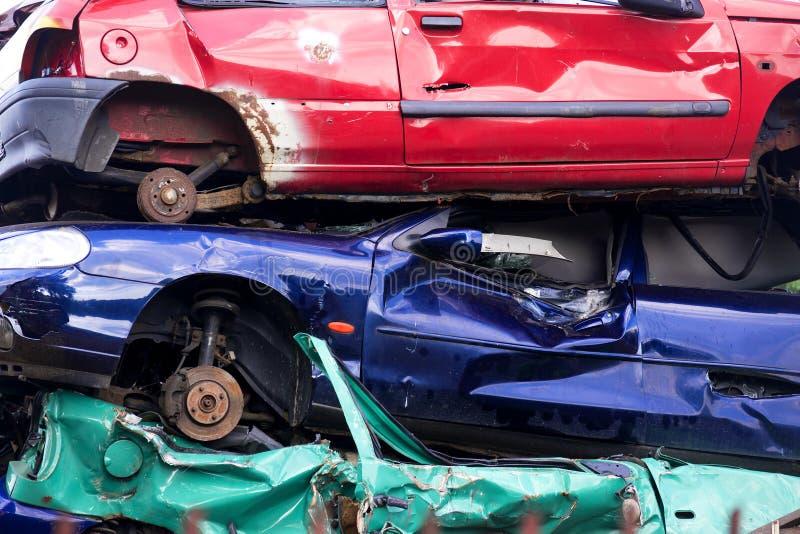 Τρία ζωηρόχρωμα απορριμμένα αυτοκίνητα απορρίματος που συσσωρεύονται σε ένα junkyard, conce στοκ εικόνα