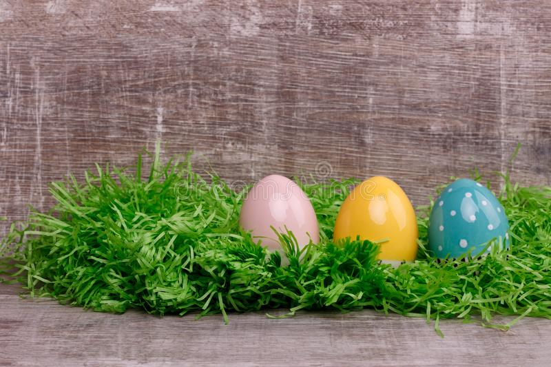 Τρία ζωηρόχρωμα αυγά σε μια πράσινη χλόη μπροστά από ένα ξύλινο υπόβαθρο διαθέσιμος χαιρετισμός αρχείων Πάσχας eps καρτών στοκ εικόνα