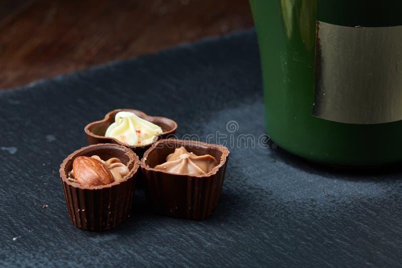 Τρία καραμέλες σοκολάτας και φλυτζάνι καφέ στην πέτρα επιβιβάζονται πέρα από το ξύλινο υπόβαθρο, εκλεκτική εστίαση, κινηματογράφη στοκ φωτογραφίες με δικαίωμα ελεύθερης χρήσης
