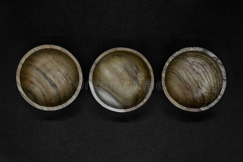 Τρία καφετιά κύπελλα που γίνονται από το ξύλο φοινίκων που τοποθετείται στη γραμμή στο μαύρο υπόβαθρο στοκ φωτογραφία
