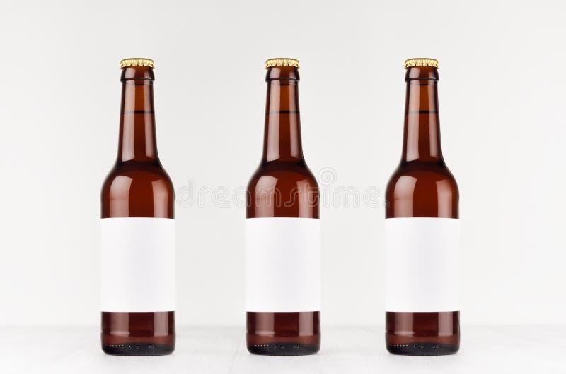 Τρία καφετιά μπουκάλια μπύρας longneck 330ml με την κενή άσπρη ετικέτα στο λευκό ξύλινο πίνακα, χλευάζουν επάνω στοκ φωτογραφία με δικαίωμα ελεύθερης χρήσης