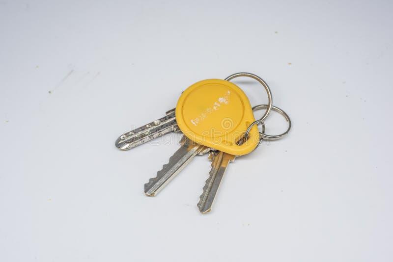 Τρία κλειδιά πορτών και μια κίτρινη κάρτα πρόσβασης στοκ εικόνες
