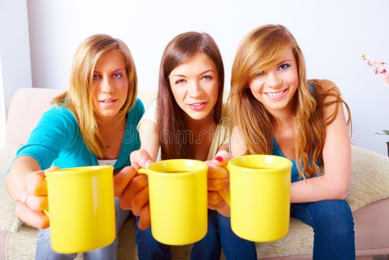 Τρία κορίτσια με τα φλυτζάνια στοκ φωτογραφία με δικαίωμα ελεύθερης χρήσης