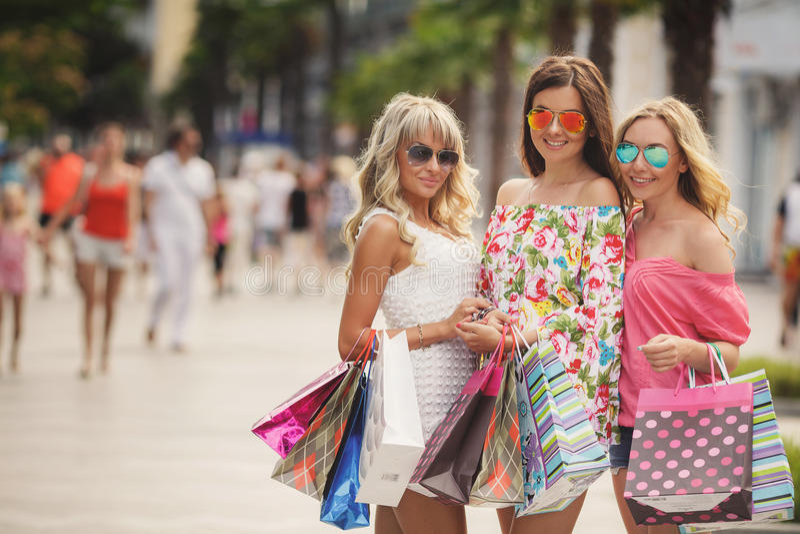 Τρία κορίτσια με τις τσάντες αγορών και πηγαίνουν στοκ φωτογραφία με δικαίωμα ελεύθερης χρήσης