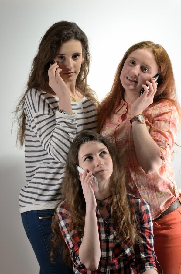Τρία κορίτσια μιλούν στο τηλέφωνο στοκ εικόνα με δικαίωμα ελεύθερης χρήσης