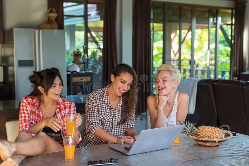 Τρία κορίτσια που κάθονται στον πίνακα χρησιμοποιούν το ευτυχές χαμόγελο φορητών προσωπικών υπολογιστών, νέοι φίλοι γυναικών από  στοκ εικόνα με δικαίωμα ελεύθερης χρήσης