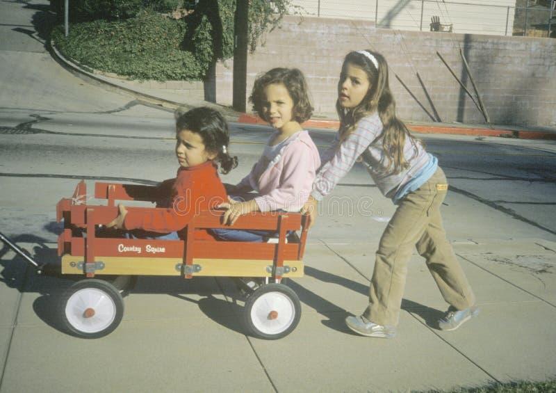 Τρία κορίτσια που παίζουν με ένα κόκκινο βαγόνι εμπορευμάτων σε Glendale, ασβέστιο στοκ εικόνες