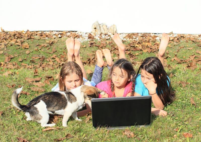 Τρία κορίτσια που παίζουν με το σημειωματάριο και το σκυλί στοκ φωτογραφία