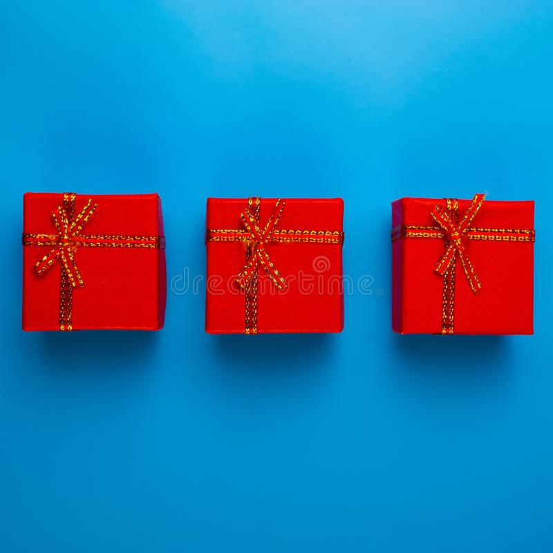 Τρία κόκκινα κιβώτια με τα δώρα Χριστουγέννων βρίσκονται σε ένα μπλε υπόβαθρο στοκ εικόνες με δικαίωμα ελεύθερης χρήσης