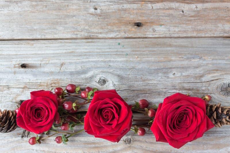 Τρία κόκκινα τριαντάφυλλα σε μια σειρά σε ένα αγροτικό ξύλινο υπόβαθρο στοκ εικόνα με δικαίωμα ελεύθερης χρήσης