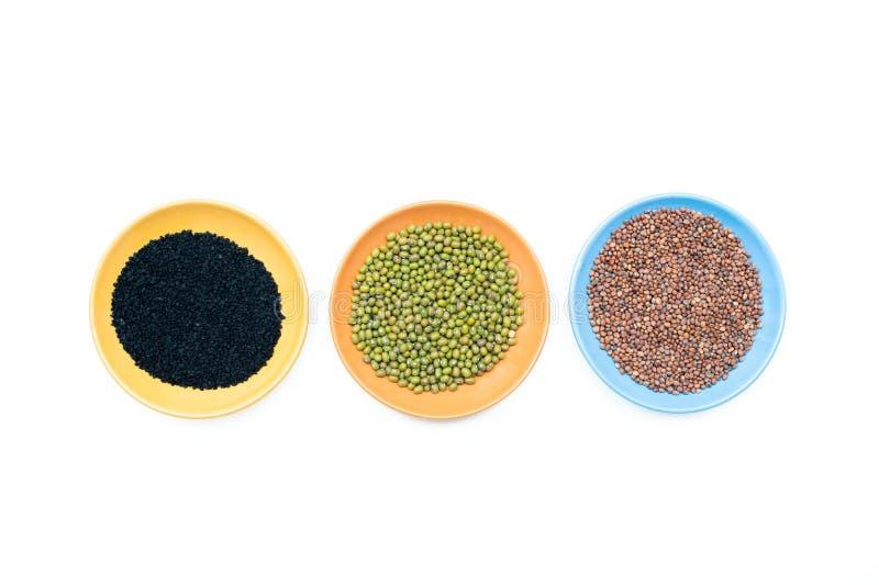 Τρία κύπελλα με τους διαφορετικούς σπόρους στο άσπρο υπόβαθρο Στοκ Εικόνες