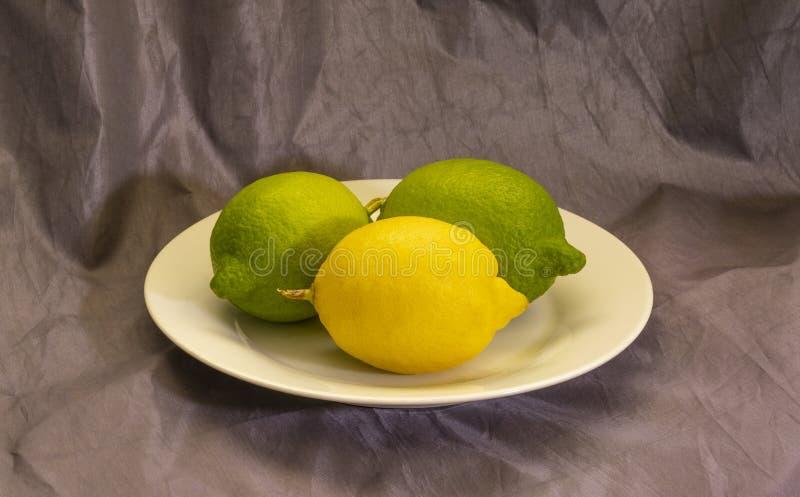 Τρία λεμόνια σε ένα πιάτο στοκ εικόνες