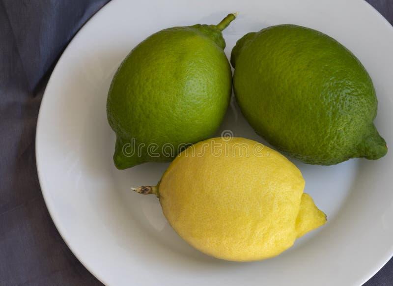 Τρία λεμόνια σε ένα πιάτο στοκ φωτογραφία