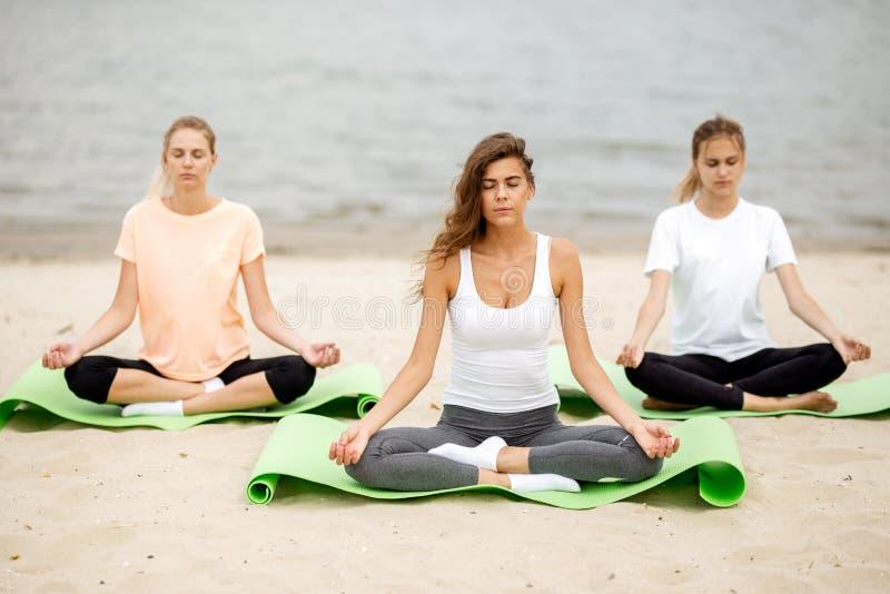 Τρία λεπτά νέα κορίτσια κάθονται σε μια γιόγκα θέτουν με το κλείσιμο των ματιών στα χαλιά στην αμμώδη παραλία δίπλα στον ποταμό μ στοκ εικόνες