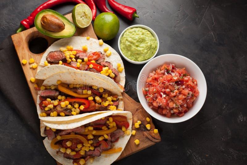 Τρία μεξικάνικα tacos με το βόειο κρέας, το μαύρους Angus και τα λαχανικά στον ξύλινο πίνακα σε ένα σκοτεινό υπόβαθρο πετρών Μεξι στοκ εικόνα με δικαίωμα ελεύθερης χρήσης