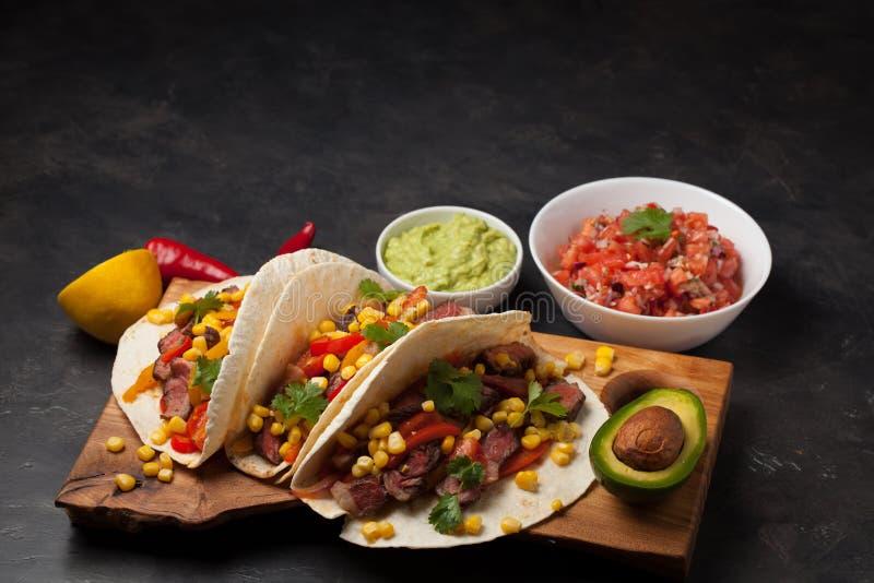 Τρία μεξικάνικα tacos με το βόειο κρέας, το μαύρους Angus και τα λαχανικά στον ξύλινο πίνακα σε ένα σκοτεινό υπόβαθρο πετρών Μεξι στοκ φωτογραφίες