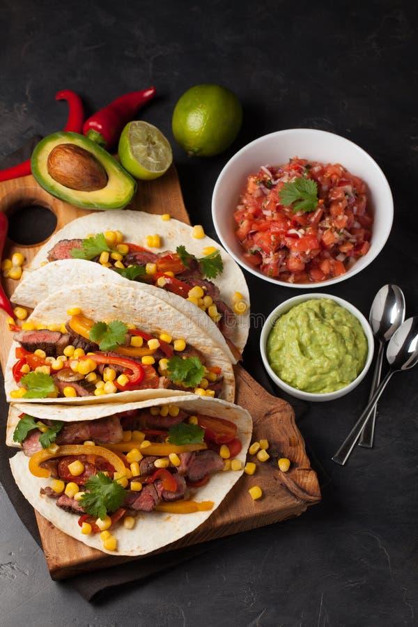 Τρία μεξικάνικα tacos με το βόειο κρέας, το μαύρους Angus και τα λαχανικά στον ξύλινο πίνακα σε ένα σκοτεινό υπόβαθρο πετρών Μεξι στοκ εικόνα