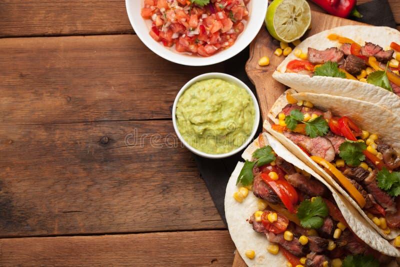 Τρία μεξικάνικα tacos με το βόειο κρέας, το μαύρους Angus και τα λαχανικά στον παλαιό αγροτικό πίνακα Μεξικάνικο πιάτο με τις σάλ στοκ εικόνα