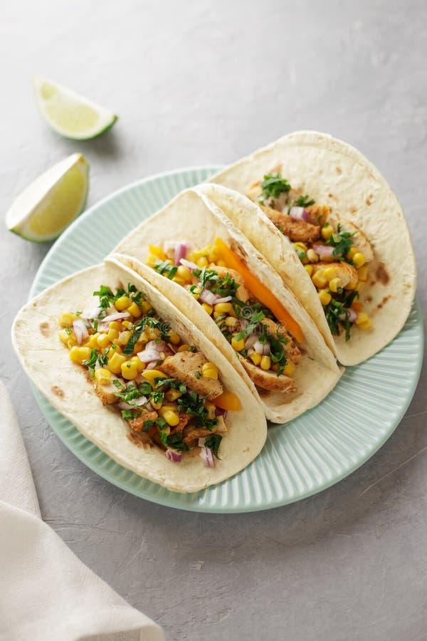 Τρία μεξικάνικα tacos με το κοτόπουλο, το καλαμπόκι, το γλυκό πιπέρι και το μαϊντανό στο μπλε πιάτο στον πίνακα στοκ φωτογραφίες με δικαίωμα ελεύθερης χρήσης